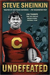A drawing of a man who is Jim Thorpe looks out to the distance from the cover. He is wearing a red jersey with a large C on it and holding a football.